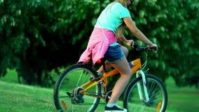 El niño puesto en casco de la bicicleta enseña a la bici del paseo en parque almacen de metraje de vídeo