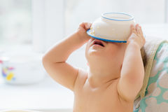 El niño puso un cuenco en su cabeza Imagen de archivo