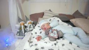 El niño que abraza un juguete mientras que duerme, niño pequeño lindo, pequeño niño duerme, bebé que miente en la cama en los res almacen de video