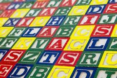 El niño que aprende el deletreo del ABC bloquea el fondo Imagen de archivo