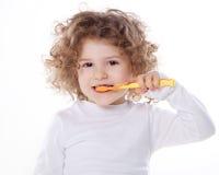 El niño que cepilla sus dientes aislados Foto de archivo