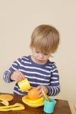 El niño que cocina y que come finge la comida Foto de archivo