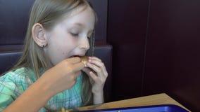El niño que come el bocadillo de la hamburguesa, retrato del niño come los alimentos de preparación rápida, cara hambrienta de la almacen de video