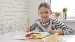 El niño que come el desayuno en la cocina, niño come los huevos sanos de la comida, verduras de la muchacha fotos de archivo
