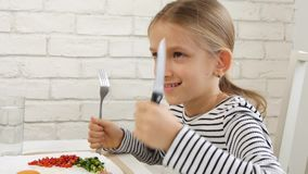 El niño que come el desayuno en la cocina, niño come los huevos sanos de la comida, verduras de la muchacha metrajes