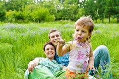 El niño que come la flor, sonriendo parents adentro detrás Fotografía de archivo