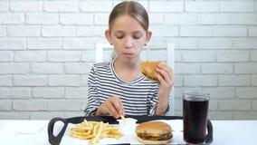El niño que come la hamburguesa en el restaurante, niño come a la niña hambrienta de los alimentos de preparación rápida de los d almacen de video