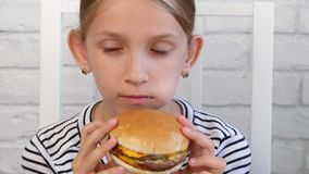 El niño que come los alimentos de preparación rápida, niño come la hamburguesa en el restaurante, jugo de consumición de la mucha almacen de metraje de vídeo