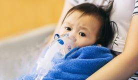 El niño que consiguió enfermo por una infección de pecho tiene cuidado con la máscara del nebulizador fotografía de archivo