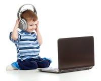 El niño que juega la computadora portátil escucha la música en auriculares fotografía de archivo