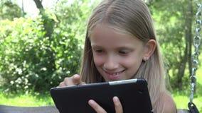 El niño que juega la tableta que balancea, muchacha utiliza la PC al aire libre en la naturaleza, niño en jardín almacen de video