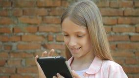 El niño que juega la tableta por la pared de ladrillos en la yarda, niña utiliza Smartphone al aire libre fotografía de archivo