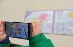 El niño que jugaba pinturas móviles aumentadas de la realidad de un color llenó la vaca vía móvil Juegos de AR y de VR fotografía de archivo libre de regalías