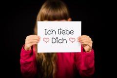 El niño que lleva a cabo la muestra con el alemán redacta el liebe Dich de Ich - te amo Foto de archivo libre de regalías