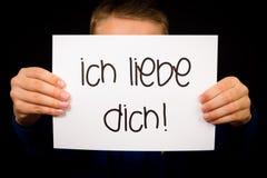 El niño que lleva a cabo la muestra con el alemán redacta el liebe Dich de Ich - te amo Imagen de archivo libre de regalías