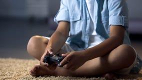 El niño que presiona la palanca de mando abotona el carácter de control en la consola, entretenimiento fotos de archivo
