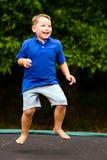 El niño que salta en el trampolín Fotos de archivo
