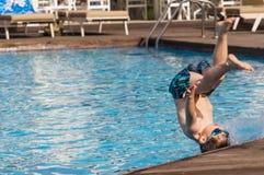 El niño que salta en la piscina Imagenes de archivo