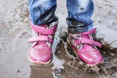 El niño que salta para los charcos en el camino, otoño, primer Imagenes de archivo