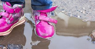 El niño que salta para los charcos en el camino, otoño, primer Fotografía de archivo