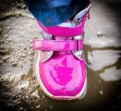 El niño que salta para los charcos en el camino, otoño, primer Foto de archivo libre de regalías