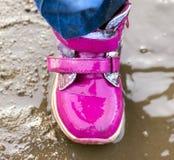 El niño que salta para los charcos en el camino, otoño, primer Imágenes de archivo libres de regalías