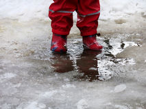 El niño que salta para los charcos en los caminos deshiela en finales del invierno imagenes de archivo