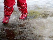 El niño que salta para los charcos en los caminos deshiela en finales del invierno Fotos de archivo