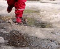 El niño que salta para los charcos en los caminos deshiela en finales del invierno Foto de archivo libre de regalías