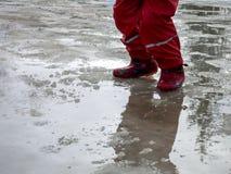 El niño que salta para los charcos en los caminos deshiela en finales del invierno Imagen de archivo libre de regalías