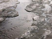 El niño que salta para los charcos en los caminos deshiela en finales del invierno Imagen de archivo
