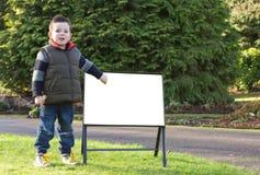 El niño que señala a un en blanco firma adentro el parque Foto de archivo libre de regalías