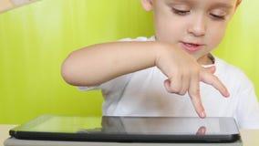 El niño que se sienta en la tabla toca la visualización electrónica de la tableta Un niño está jugando con un ordenador portátil  metrajes