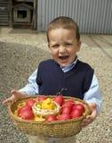 El niño que sostiene una cesta eggs Foto de archivo libre de regalías