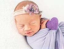 El niño recién nacido en banda y manta floridas, aseguró con una trenza fotografía de archivo