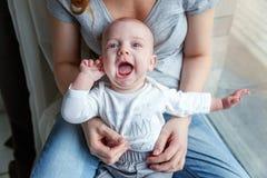 El niño recién nacido ríe en los brazos de su madre Foto de archivo libre de regalías