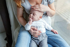 El niño recién nacido ríe en los brazos de su madre Imagen de archivo