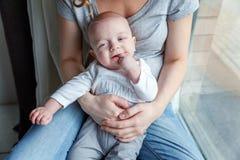El niño recién nacido ríe en los brazos de su madre Foto de archivo