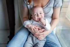 El niño recién nacido ríe en los brazos de su madre Fotografía de archivo