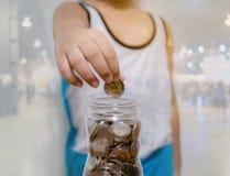 El niño recoge el dinero de ahorro para el futuro imágenes de archivo libres de regalías