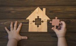 El niño recoge la casa de rompecabezas en la tabla Foto de archivo