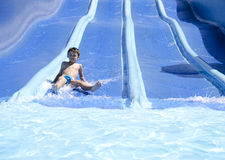 El niño resbala un waterslide Imagen de archivo libre de regalías