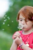 El niño rojo del pelo sopla en una flor Imágenes de archivo libres de regalías