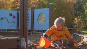 El niño rubio caucásico juega en hoyo de arena con el coche del juguete metrajes