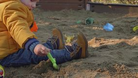 El niño rubio caucásico juega en hoyo de arena con el coche del juguete almacen de metraje de vídeo