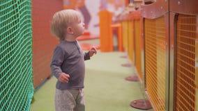 El niño rubio con los ojos azules mira la cámara con susto y da vuelta a su cabeza almacen de video