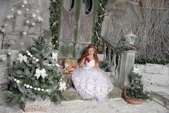 El niño rubio hermoso de la muchacha en un vestido blanco elegante se está sentando en el pórtico de la Navidad imágenes de archivo libres de regalías
