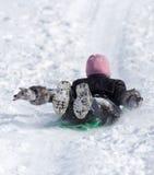 El niño rueda abajo la colina en invierno Fotos de archivo