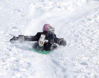 El niño rueda abajo la colina en invierno Imagen de archivo libre de regalías