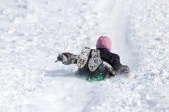 El niño rueda abajo la colina en invierno Imagenes de archivo
